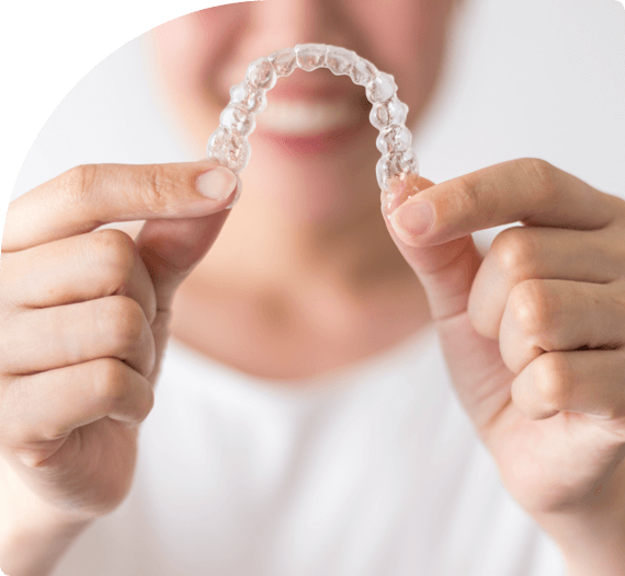 A smiling woman holds invisalign braces