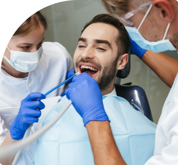 A periodontist and dental assistant performing a procedure on a patient