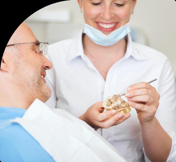 A dentist explains a procedure to a patient at Pretoria Bridge Dental