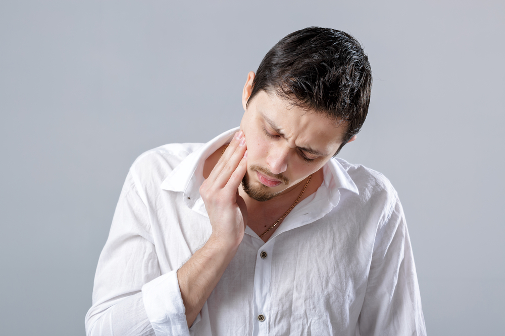man suffering from tooth pain emergency